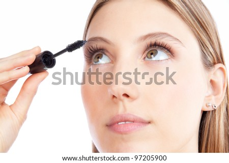 Beautiful woman applying mascara on her eyelashes. - stock photo