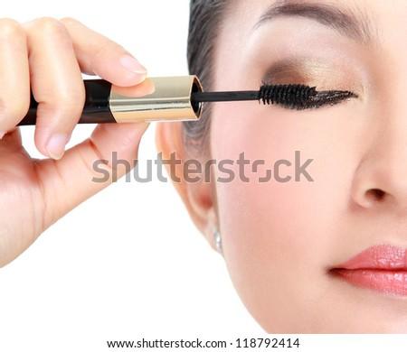 Beautiful woman applying mascara on her eyelashes isolated on white background - stock photo