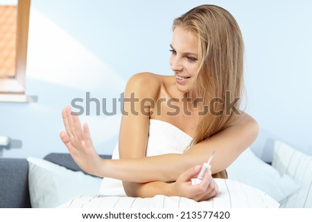 beautiful woman applying red nail polish in bed at home - stock photo