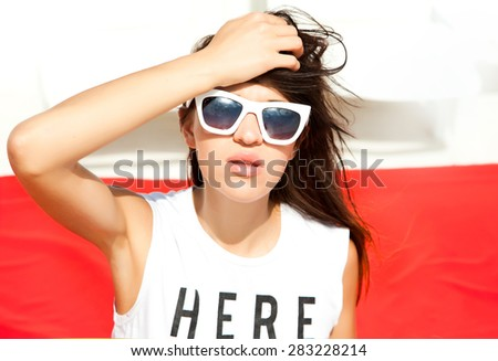 Beautiful woman arms outstretched smiling and looking at camera beside the sea cafe - stock photo