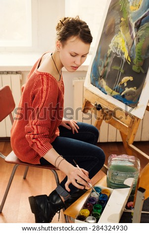 Beautiful woman artist drawing her picture on canvas with oil colors in home art studio