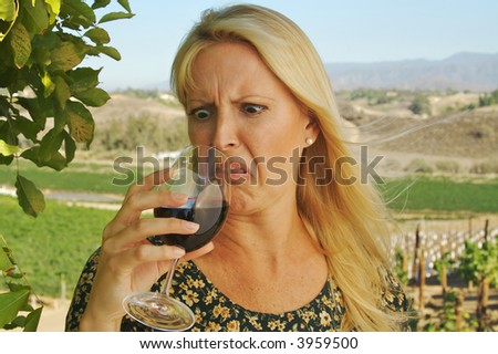 Beautiful woman at a country winery wearing her sun dress on a summer day. Apparently the wine is not so good there. - stock photo