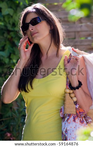 Beautiful woman at a shopping center, calling