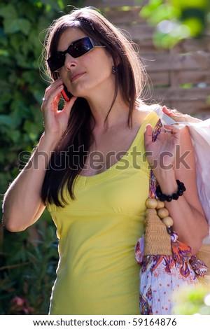 Beautiful woman at a shopping center, calling - stock photo