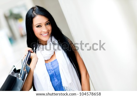 Beautiful woman at a shopping center smiling - stock photo