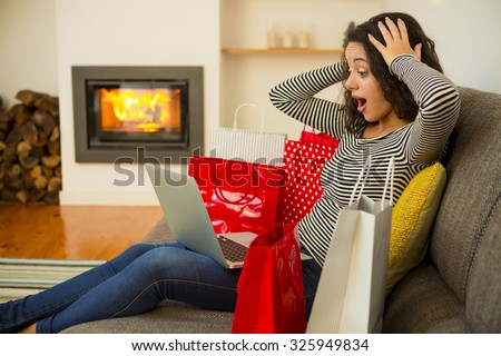 Beautiful woman at home at the warmth of the fireplace, shopping online - stock photo