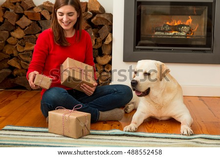 Beautiful woman at home holding some Christmas presents in the company of her dog