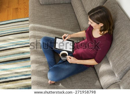 Beautiful woman at home in the sofa and working with a tablet - stock photo