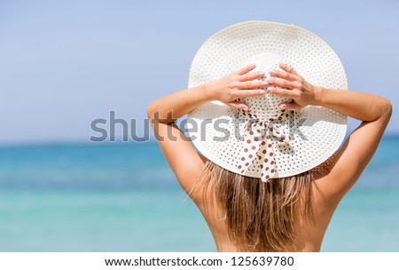 Beautiful woman at the beach wearing a hat - stock photo