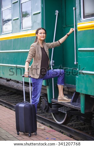 beautiful woman at the door of an old passenger railcar. the journey begins - stock photo