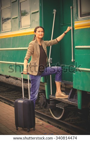 beautiful woman at the door of an old passenger railcar. the journey begins. instagram image filter retro style - stock photo