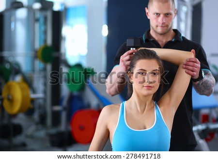Beautiful woman at the gym exercising with her trainer - stock photo