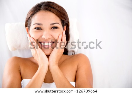 Beautiful woman at the spa lying on a bed for a massage - stock photo