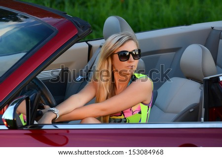 Beautiful woman at wheel the red car - stock photo
