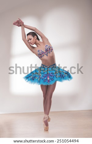 beautiful woman ballet dancer posing in front of window light - stock photo