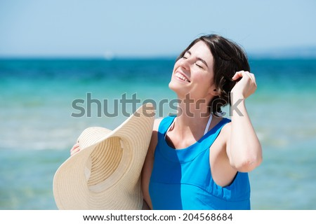 Beautiful woman basking in the sun standing on a tropical beach in front of a calm blue ocean with her head tilted to the sun and a lovely happy smile on her face as she holds her straw sunhat - stock photo