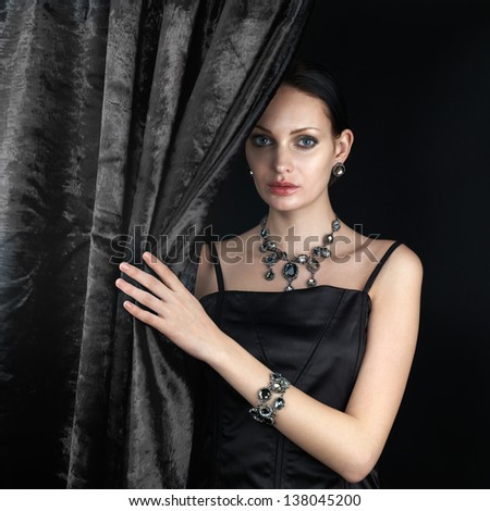 Beautiful woman behind the curtain on dark background - stock photo