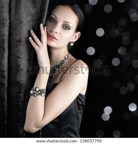 Beautiful woman behind the curtain on dark sparkling background - stock photo