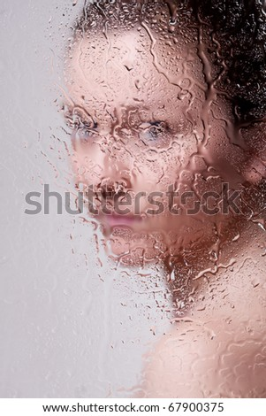 Beautiful woman behind the glass with water drops looking directly at camera - stock photo