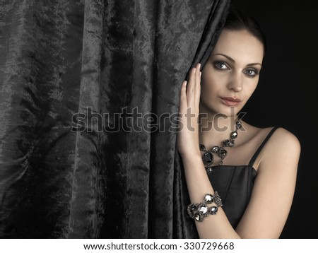 Beautiful woman behind the velvet curtain on dark background - stock photo