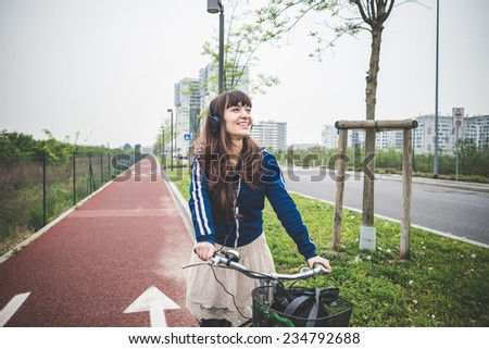 beautiful woman biker cycling in a desolate urban landscape - stock photo