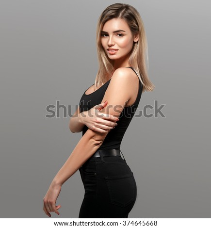 Beautiful woman blond full length portrait young studio on gray in black jeans  - stock photo