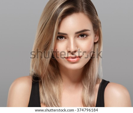 Beautiful woman blonde hair portrait close up studio on gray - stock photo