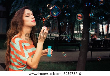 beautiful woman blowing bubbles in the park - stock photo