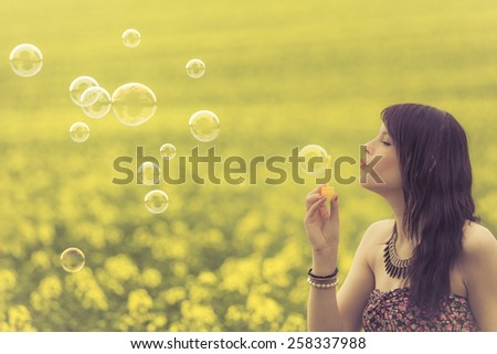 Beautiful woman blowing many soap bubbles in summer nature. The girl has fun in a yellow meadow and is enjoying her youth. - stock photo