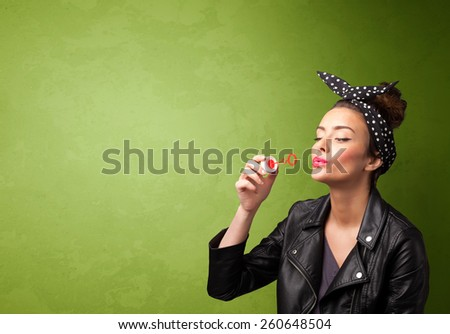 Beautiful woman blowing soap bubble on copyspace green background - stock photo