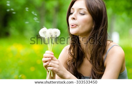 Beautiful woman blows dandelions in the park. Concept of nature and rest - stock photo