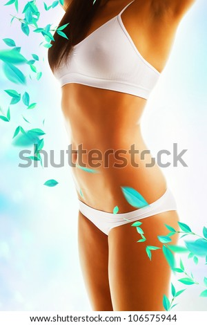 Beautiful woman body with white clothes and leaves - stock photo