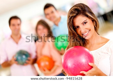Beautiful woman bowling holding a ball with friends and smiling - stock photo