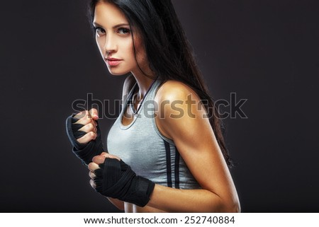 beautiful woman boxer portrait over dark background - stock photo