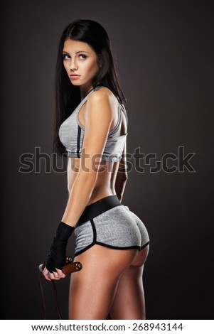 beautiful woman boxer with skipping rope portrait over dark background - stock photo