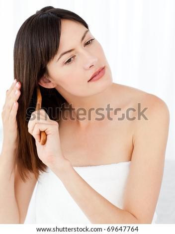 Beautiful woman brushing her hair at home - stock photo
