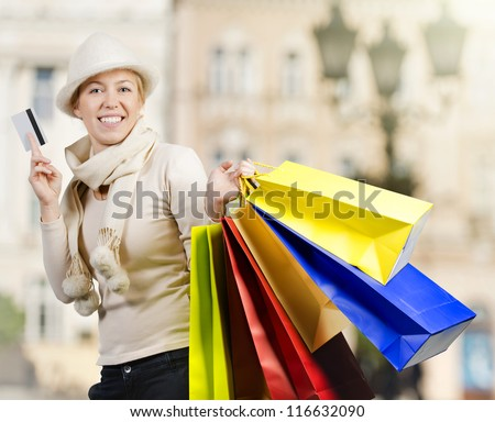 Beautiful woman carrying a lot of colorful shopping bags down town - stock photo