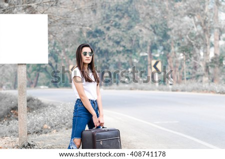 beautiful woman carrying a suitcase on a countryside road, traveller girl on the road-holiday and lifestyle concept