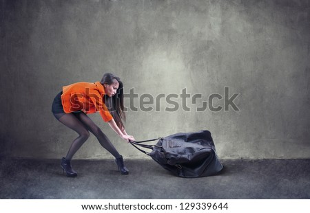 Beautiful woman carrying heavy bag  with some difficulty - stock photo