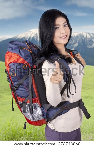 Beautiful woman carrying rucksack for hiking on the mountain, showing thumb up on the camera