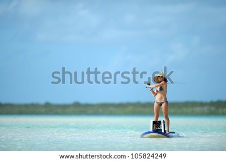 Beautiful woman casting fishing rod while paddleboarding in the Caribbean
