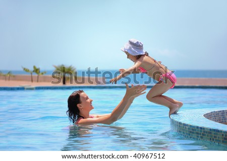 beautiful woman catches little girl jumping in pool against sea - stock photo