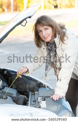Beautiful woman checking engine oil level  - stock photo