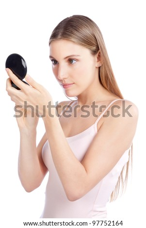 Beautiful woman checking herself with compact mirror. - stock photo