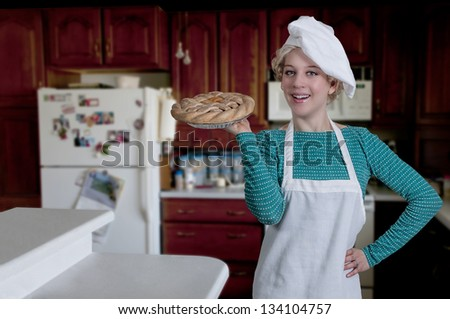 Beautiful woman chef holding a freshly baked pie