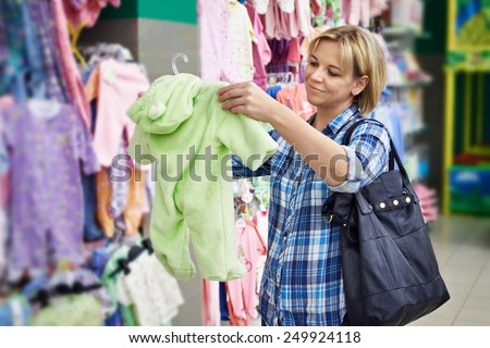 Beautiful woman chooses rompers in store - stock photo