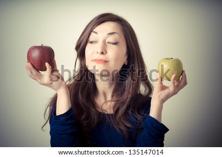 beautiful woman choosing red or yellow apples on gray background