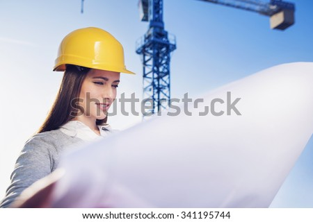 beautiful woman civil engineer viewing project plans in front of a crane - stock photo
