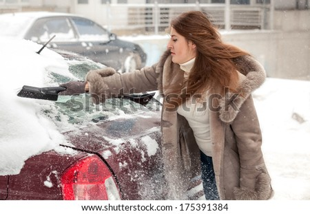 Beautiful woman cleaning car at blizzard - stock photo