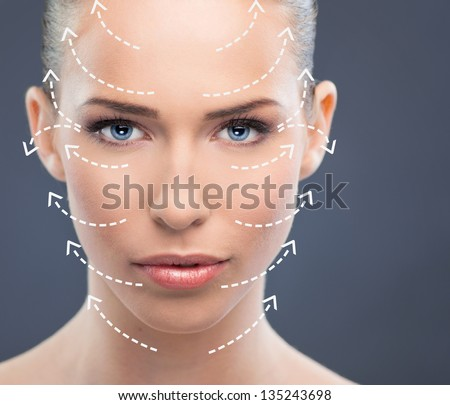 Beautiful woman close up over a  blue background with arrows - stock photo